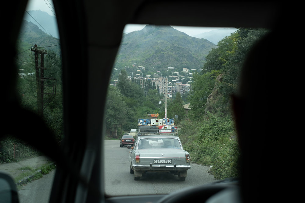 A car with a roof rack freight goods on a winding road in Armenia