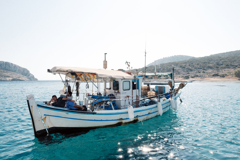 A local fishing boat and crew on the shores of Symi in Greece
