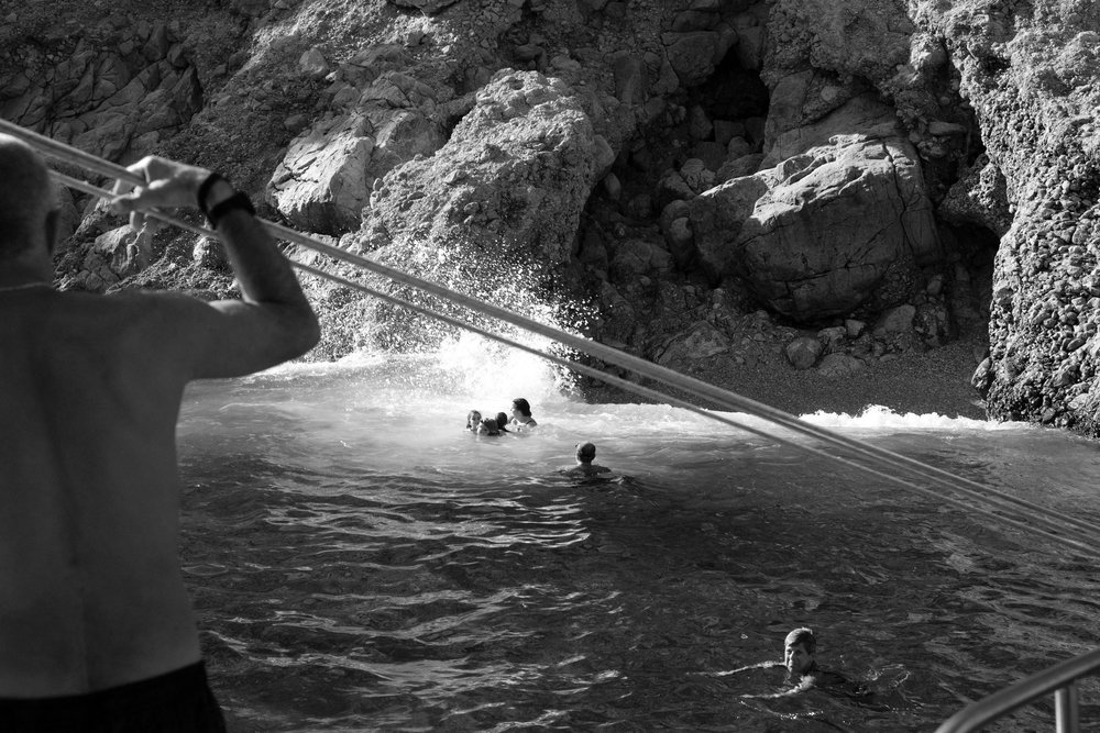 Tourist swimming from the boat at St. George during a round island cruise of Symi in Greece