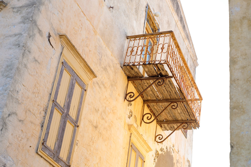 A yellow house with a balcony in Symi, Greece