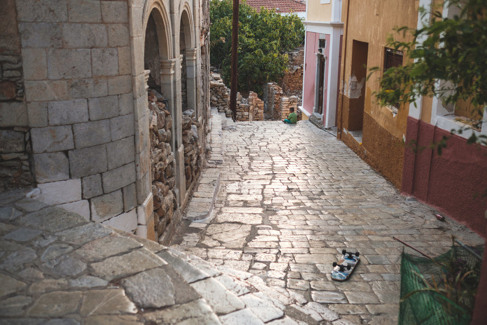 a boy takes a break during play on quiet cobble stone street in the hills above symi in greece