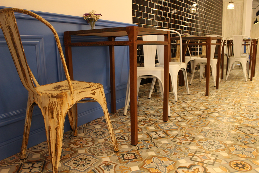 The interior of Herbera Artisan Bakery features multicoloured tiles and rustic furniture.