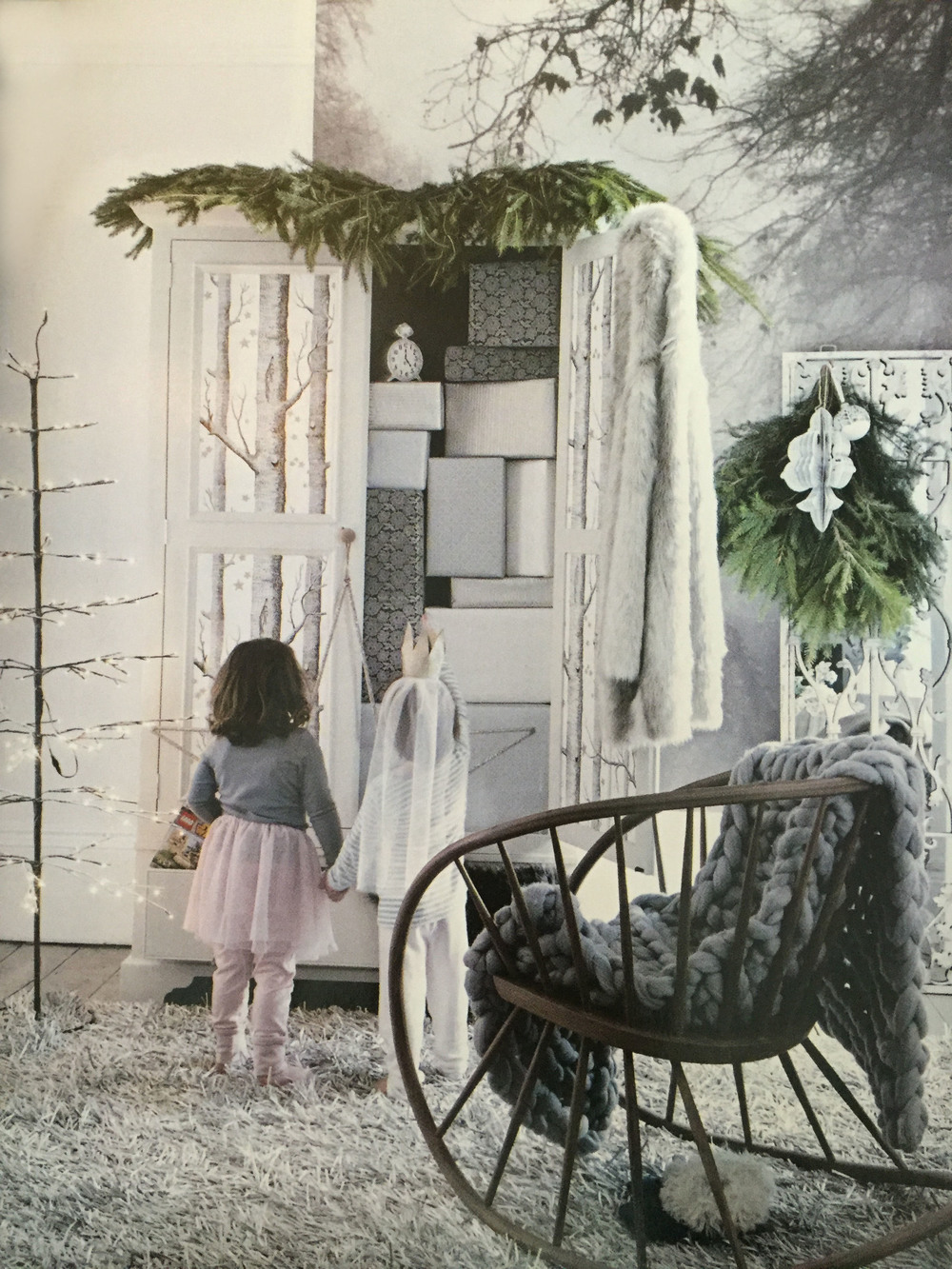 Two little girls admire the presents stacked up in a Narnia-style wardrobe. Nativ Scandinavia Blush tulle skirt with organic cotton belt, £39.00