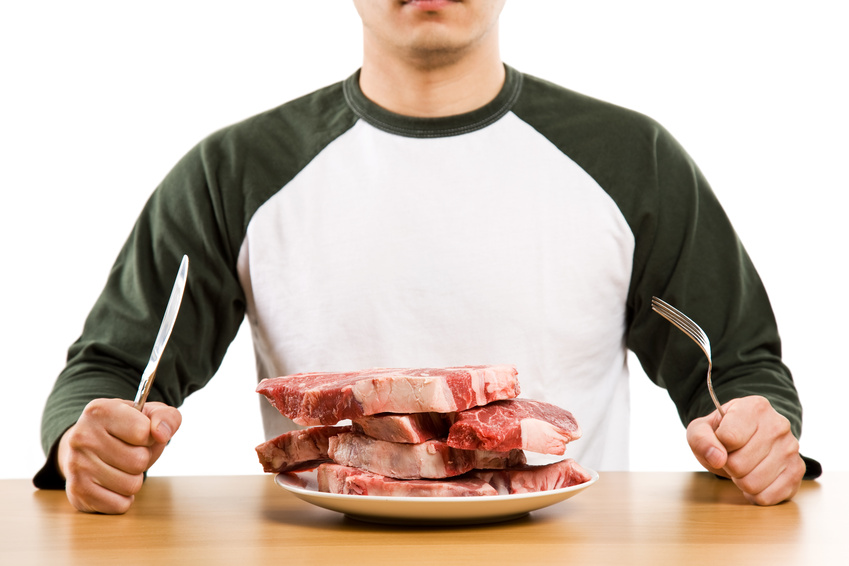 A man holding a knife and a fork with a stack of raw steak