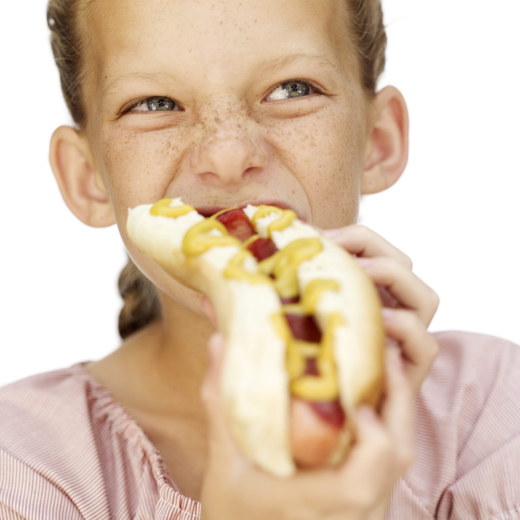 Young Girl Eating a Hotdog