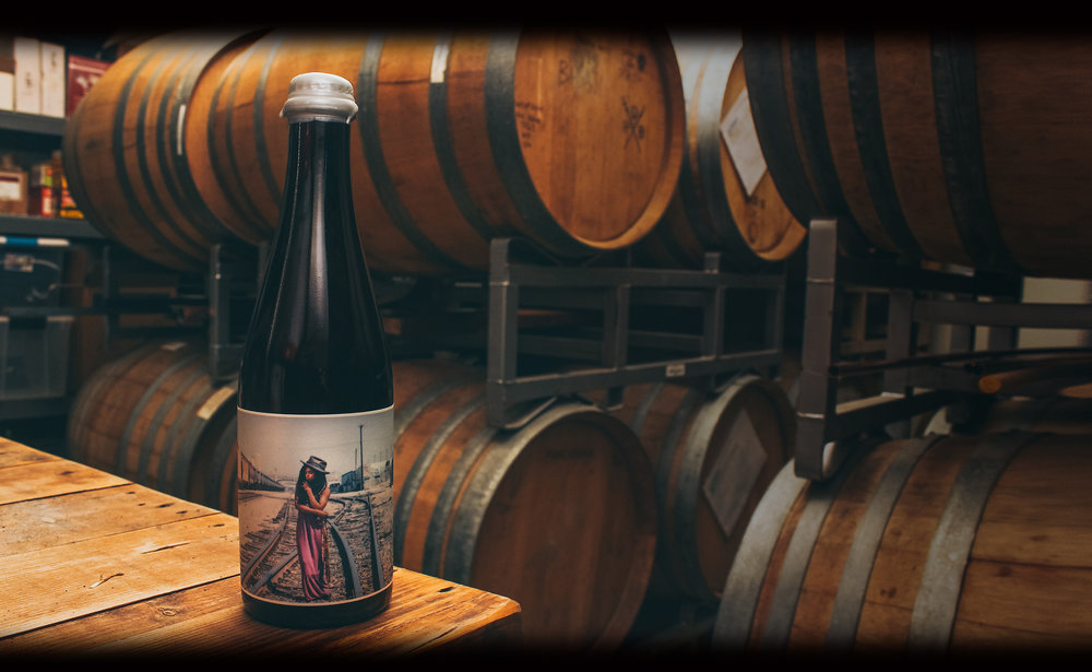 BRUXELLA  ABV 5 | IBUS 15   RELEASED:  AUGUST 2017  An evolving take on the Flemish Red Ale, this garnet hued sour ale rested in Dry River Oak for close to 3 years. All the red fruit aromas, soft acidity, and rich oak tannin that Flanders is known for. Made in East LA, with wild yeast cultured in East LA.   TASTING NOTES   Rich aromas of Cherries and black currants are elevated by moderate acidity, while the years of resting in oak contribute a strong tannin which fills out the body of the beer, and rounds out the back end of the palate.  Our Take  While Bruxella may be the closest we get to brewing traditional styles, the extended barrel time means that this beer only surfaces once in a great while, get your hand waxed bottles before they are gone for another 3 years.
