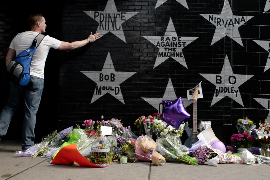 A fan pays his respects to Prince at an impromptu memorial for the musician that was set up at First Avenue in Minneapolis, Minn., by mourners the day the musician died, Thursday, April 21, 2016 (visit my multimedia page to see a video I did covering the reaction of fans to Prince's death).