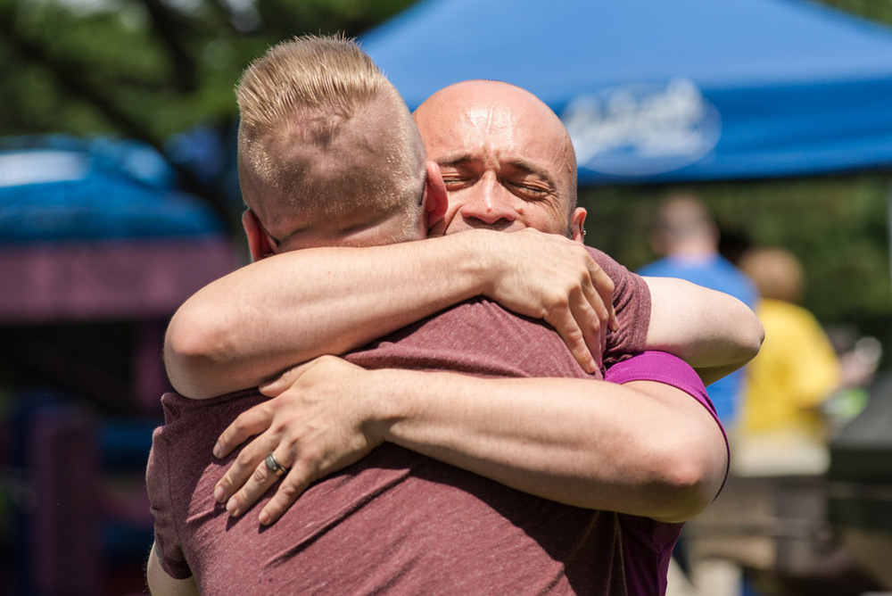 Carlos Antonio Saldana embraces his friend David Brink while attending Golden Valley Pride Festival, in Golden Valley, Minn., Sunday, June 12, 2016. Saldana is originally from Orlando, Fla., and was emotionally struck by the news of the shooting at Pulse nightclub as he is familiar with it and has friends that go there sometimes. Saldana said at this point he does not know anyone who was there at the time of the shooting.