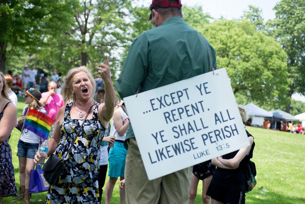 "Mara Glubka, of Richfield, Minn., yells at a yells at a Christian protester while attending Golden Valley Pride Festival, in Golden Valley, Minn., Sunday, June 12, 2016.  She was so upset when protesters started to quote the Bible saying all homosexuals are sinners and in response yelled, ""Shout them down! Shout them down!"""