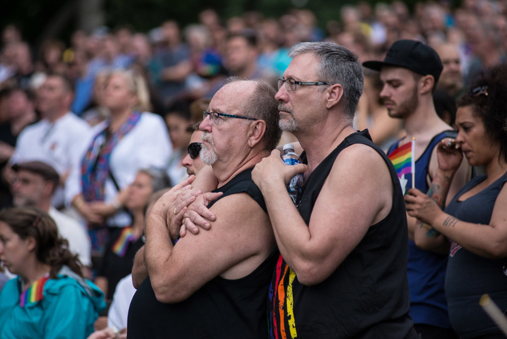 Two men listen to speakers as hundreds of mourners gathered for an emotional vigil to show their support for the victims of the shooting at Pulse nightclub in Orlando, Fla., at Loring Park in Minneapolis, Minn., Sunday, June 12, 2016.