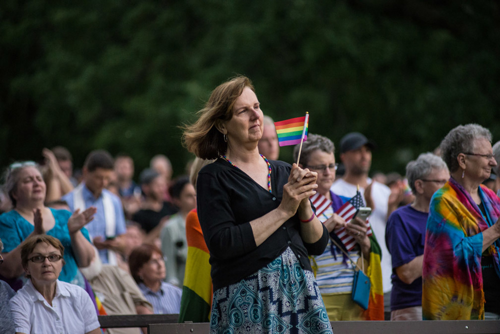 Stephanie Peck, of Burnsville, Minn., holds a pride flag while attending a vigil held for the victims of the shooting at Pulse nightclub in Orlando, Fla., at Loring Park in Minneapolis, Minn., Sunday, June 12, 2016.