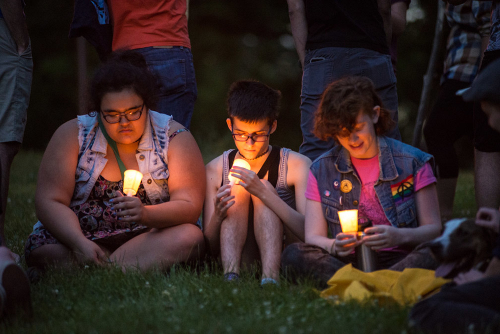 From left, Hattie Hsu, Steph Theisen, and Chandler Daily, all of St. Paul, Minn., hold candles they lit while attending a vigil held for the victims of the shooting at Pulse nightclub in Orlando, Fla., at Loring Park in Minneapolis, Minn., Sunday, June 12, 2016.