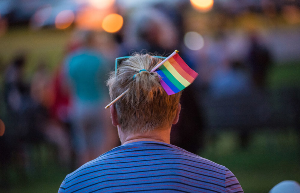 A young man wears a rainbow flag in his pony tail while among hundreds who came out for an emotional vigil to show their support for the victims of the shooting at Pulse nightclub in Orlando, Fla., at Loring Park in Minneapolis, Minn., Sunday, June 12, 2016.