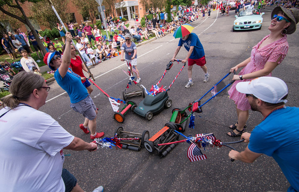 Members of the Lawn Mower Brigade from left, Irene Opsahl, Erin Stutelberg, Megan Tracey, Joan Maland, Chuck Tracey, Elizabeth Clark, and Jonathon Carter perform their routine on Knapp Avenue during the 4th In The Park Parade in the St. Anthony Park neighborhood in St. Paul, Minn., Monday, July 4, 2016.
