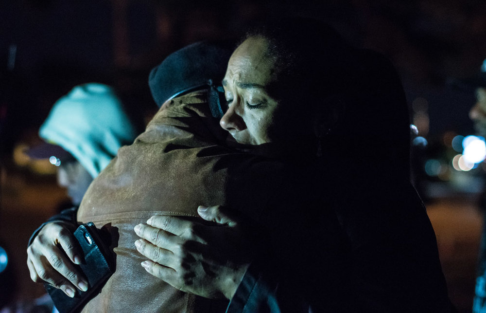 Overcome with emotion a woman, who wished to remain unidentified, hugs a friend while attending a vigil at the site where Philando Castile was shot and killed by a St. Anthony police officer during a traffic stop in Falcon Heights, Minn., three months after the incident on Friday, Oct. 7, 2016.