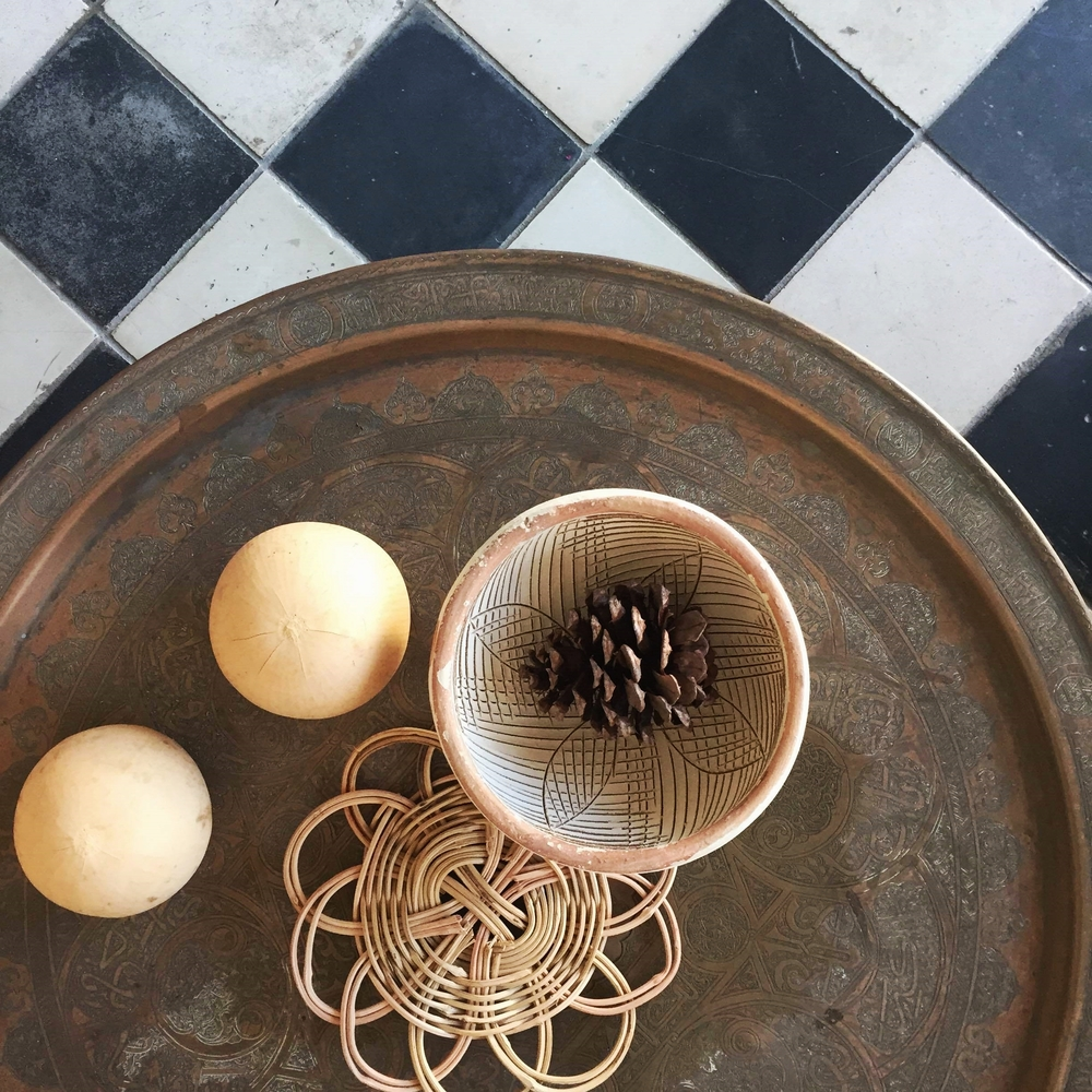 Subtle seasonal accents show up on one of our side tables: Dried gourds, a pine cone and a palette of earth tones.