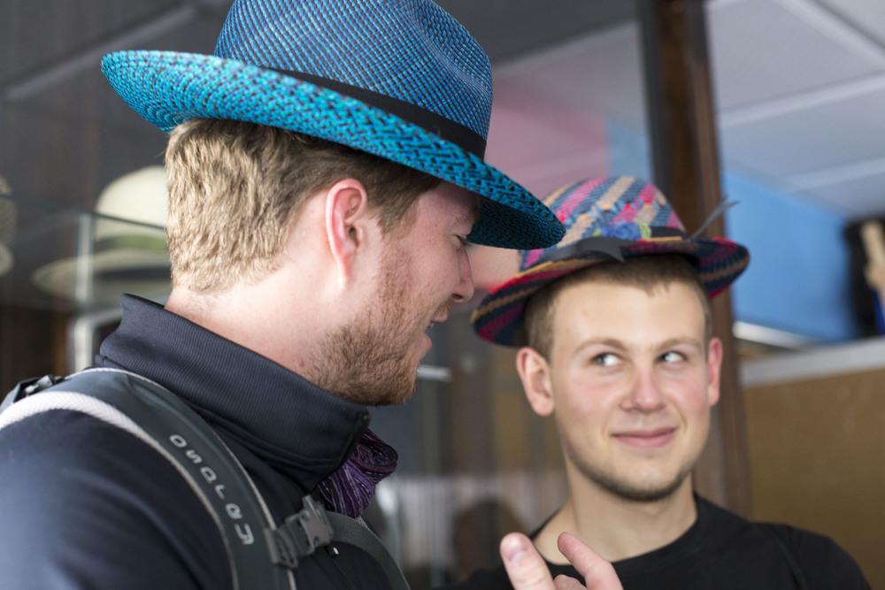 Aidan and Matt try on some handmade straw hats.