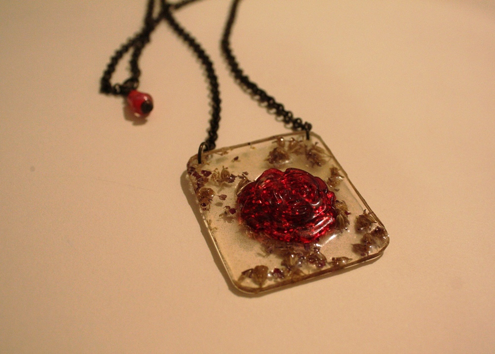 My friend fabricated this pendent by making a mold in which to pour apoxy, dried flowers and red sparkles into.