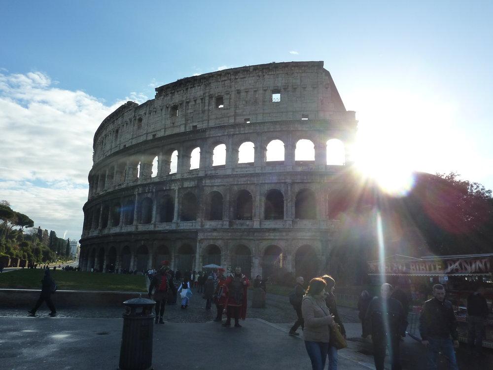 Tidiga turister och morgonsol vid Colosseum.