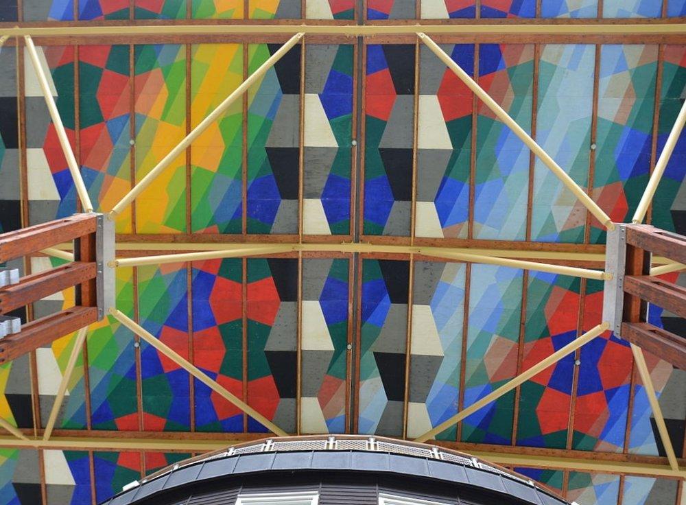 Undersidan på taket på Måltidens hus ser ut som regnbågsmosaik.