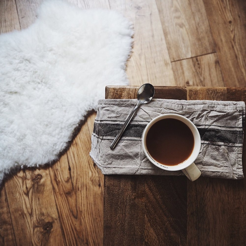 Cup of tea on a wooden table on sheepskin rug.jpg