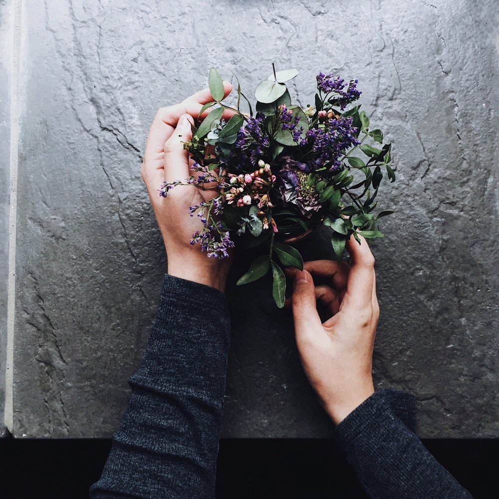 Hands holding flowers on a slate windowsill.jpg