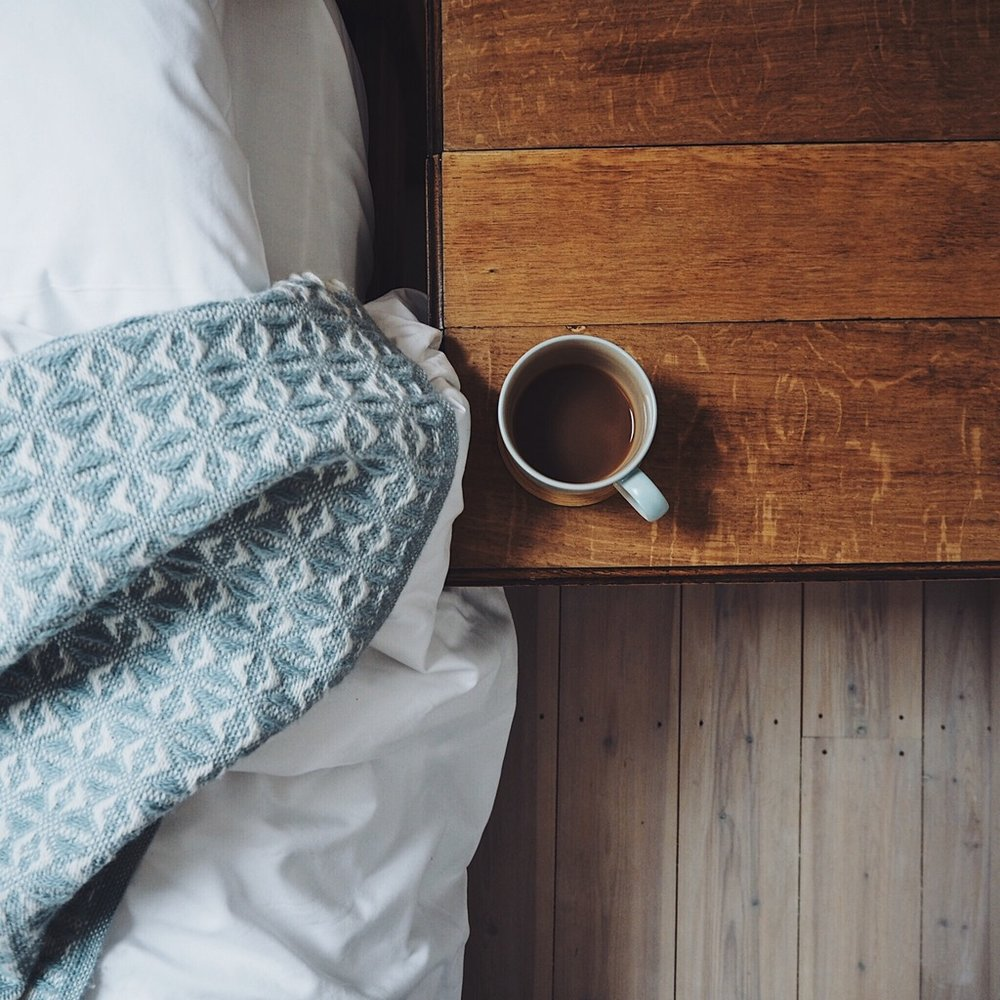 Cup of tea next to a bed with a blue blanket.jpg