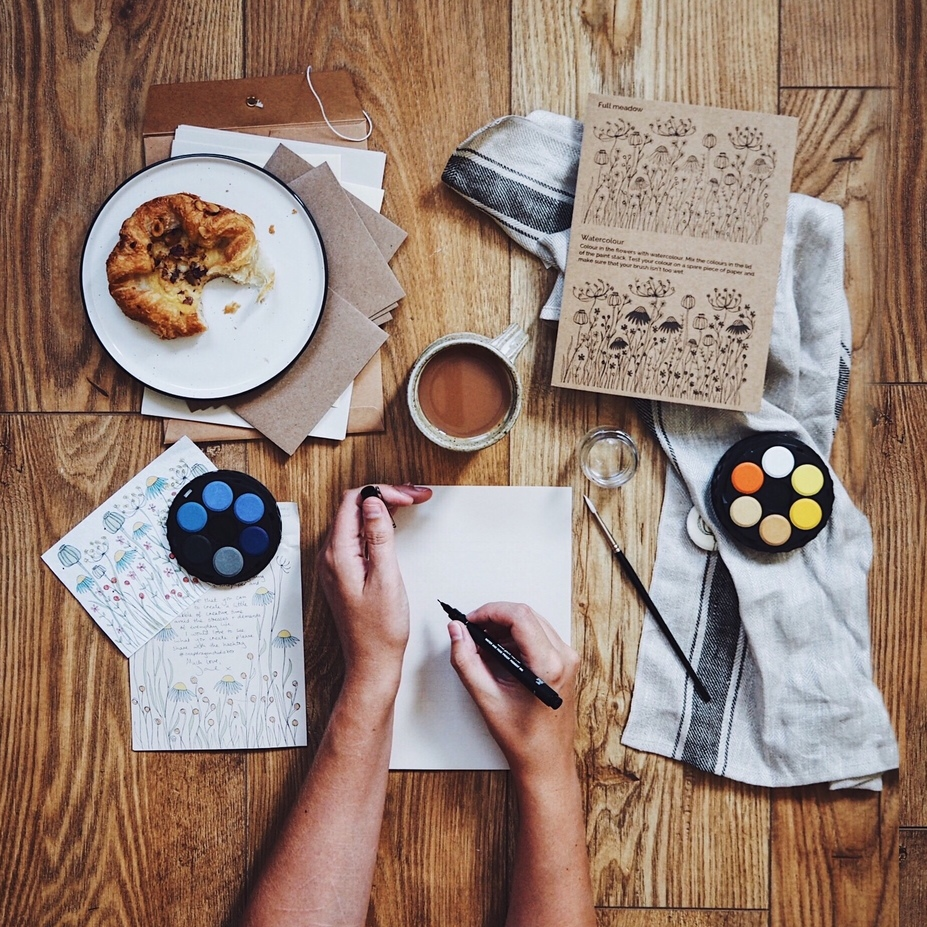 Art supplies laid out on a table with hands drawing.jpg