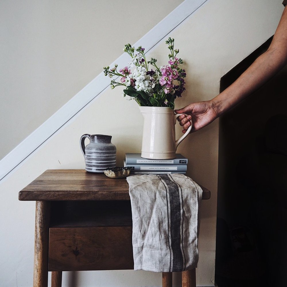 Hand holding a jug of pastel flowers on a pile of books on a side table.jpg