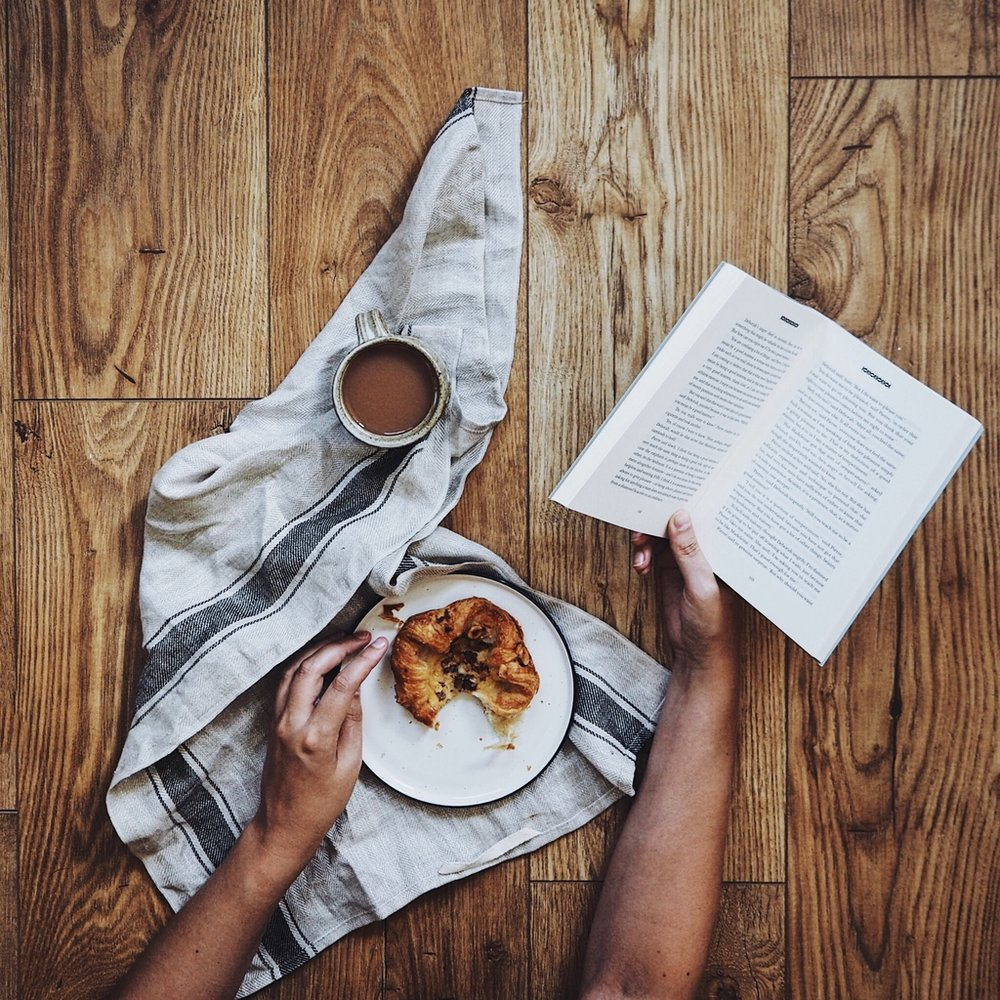 Hands holding a book with a cup of tea and pastry on a table.jpg