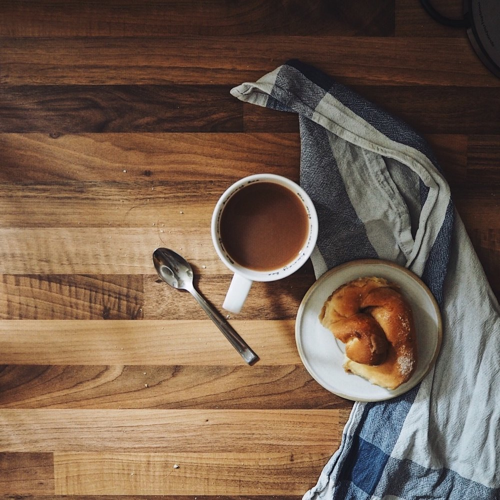 Cup of tea and a cake on a wooden surface.jpg