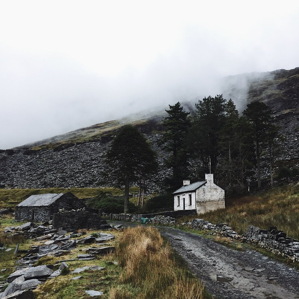 Little white cottage next to a lake in misty mountains.jpg