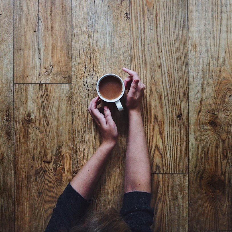 Girls hands holding a cup of tea on a wooden table.jpg