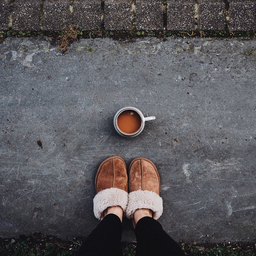 Brown slippers and cup of tea on a grey step.jpg