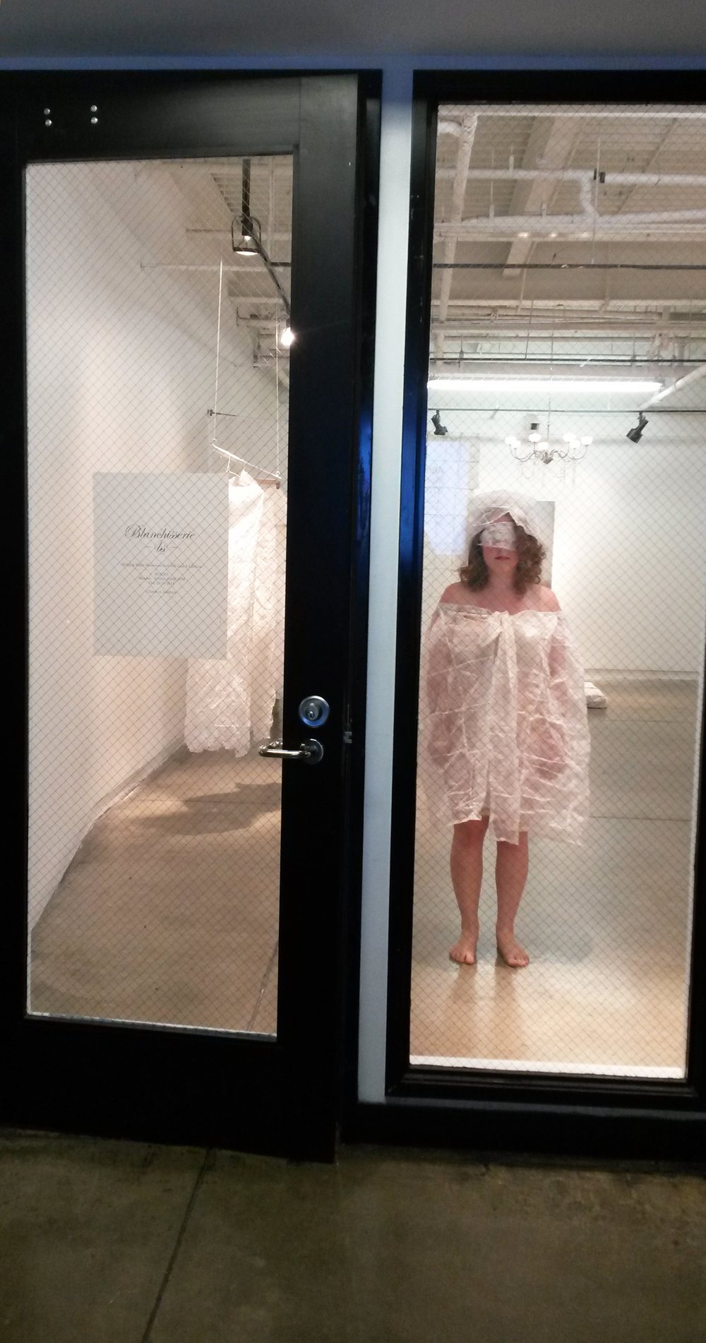 """documentation of the performance: mannequins and sales associate; photograph taken from the outside of the gallery during """"store hours"""""""