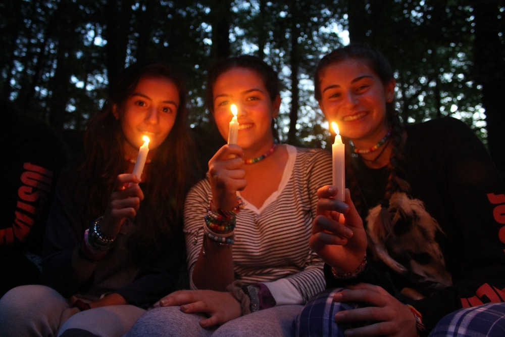 Senior girls light their candles at the end of the campfire to make a wish.