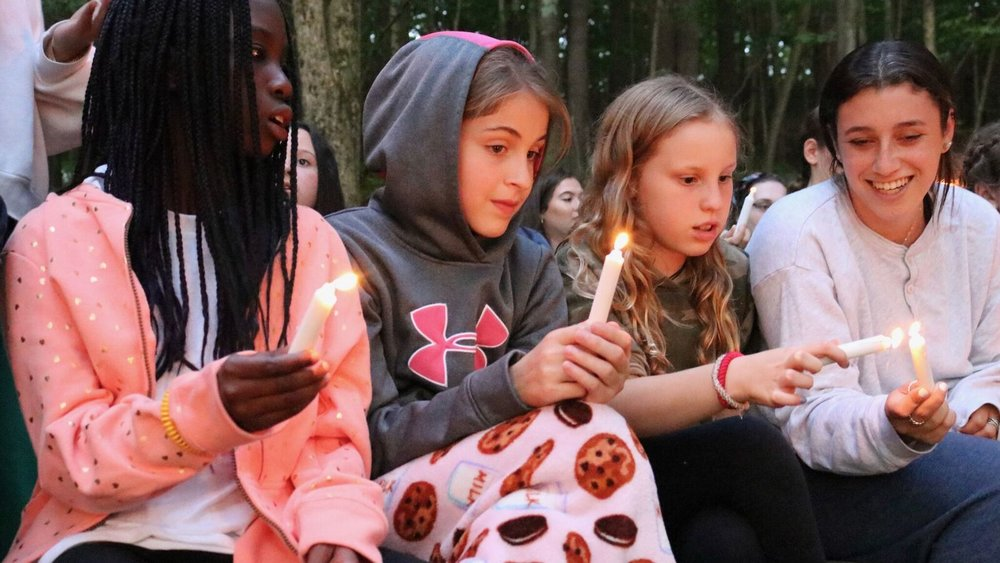 An Iconic Scatico Moment:   Sienna, Olivia, Kate, and Rachel light their candles at the Opening Campfire.