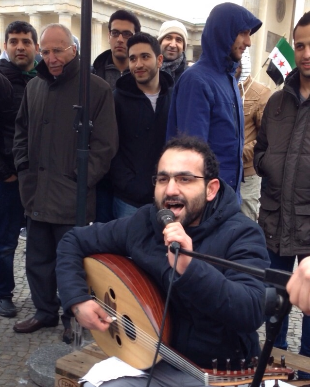 Raman Khalaf is one of the musicians who contributed to Kaan Wafi's music, playing Oud. Here he sings at the fourth anniversary of the Syrian uprising in March 2015 in Berlin. Source: Kaan Wafi