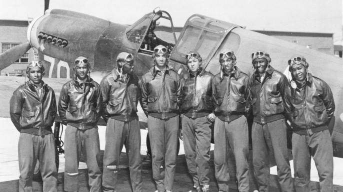 Eight Tuskegee airmen pose in front of a P-40 fighter in 1942 or 1943./History.com