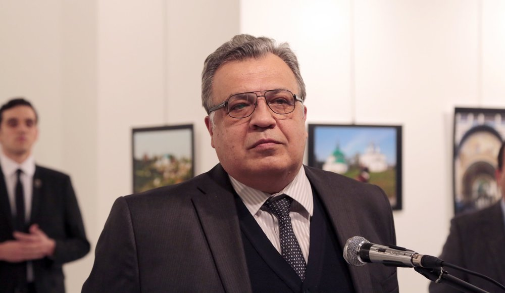 Photo of Karlov taken moments before he was assassinated. Karlov's assassin is seen in the background on the left. Credit: Burhan Ozbilici/AP