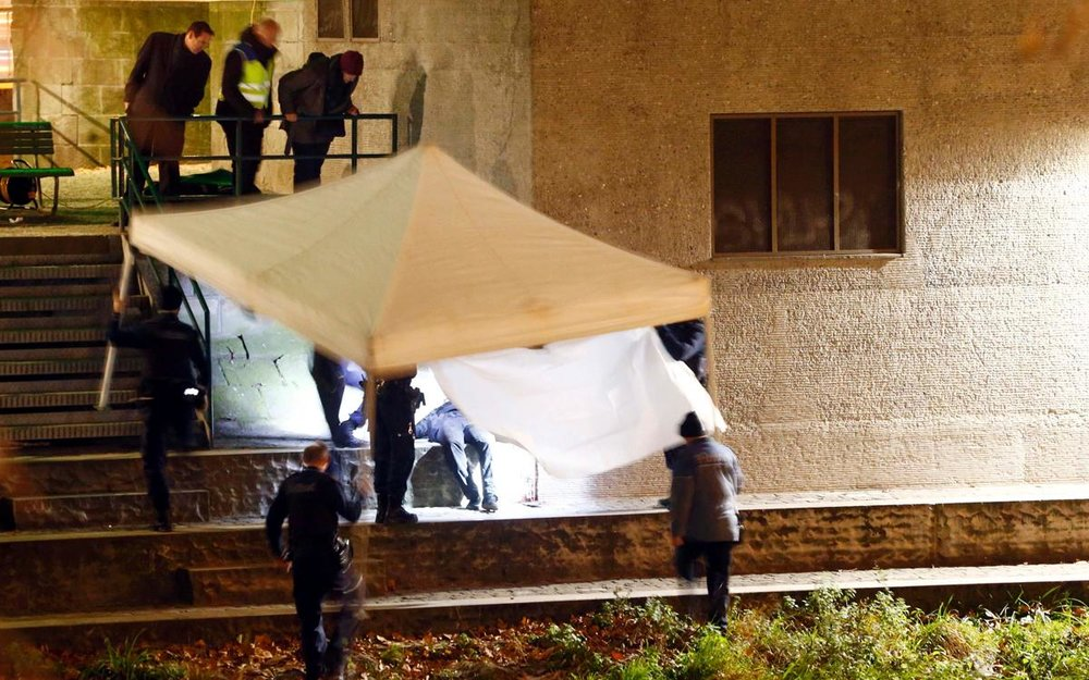 Body of suspect found near the mosque, is covered by police. Credit  ARND WIEGMANN/REUTERS