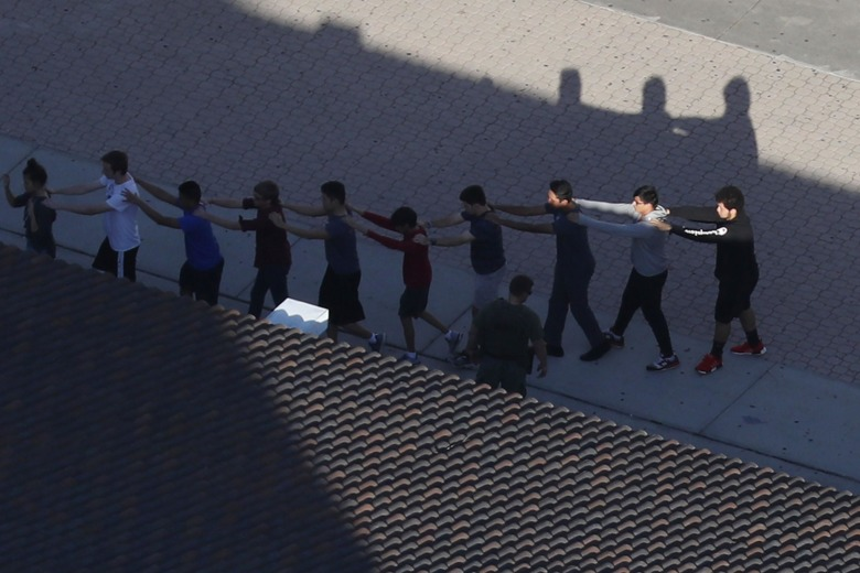 Students at Marjory Stoneman Douglas HS march out of school linked, following a mass shooting credit: Joe Raedle/Getty Images