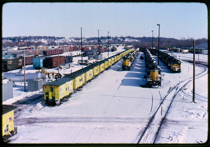 Chicago NorthWestern cabooses and engines parked at Shortline Yard waiting to be retired. Union Pacific later purchased CNW and obtained this yard. Photo circa 1984.