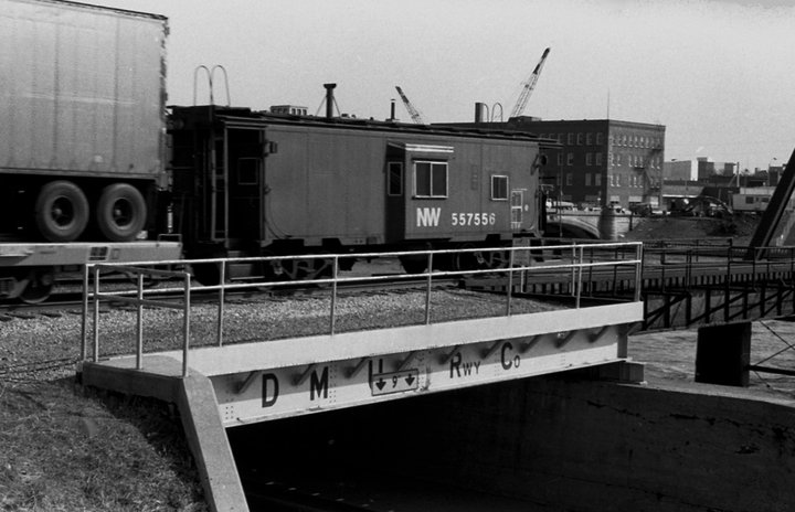 """N&W Caboose, train headed west after passing over the """"Red Pedestrian"""" bridge, once owned by the Des Moines Union Railway Company. Notice the short bridge over what was once called """"Riverside Drive"""", which has since been converted into a bike trail, and floods regularly. Photo circa 1983."""