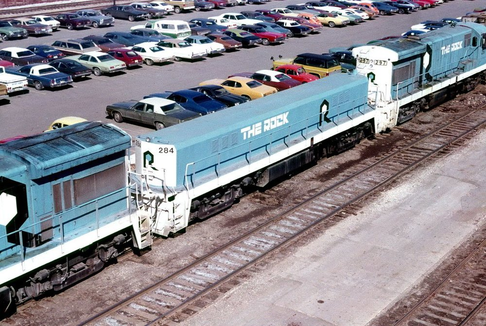 """Having only recently  been repainted a sky blue and renamed """"The Rock"""" in 1976, these engines, including the Slug seen at center, were purchased by the newly formed IAIS and await repainting near the 7th St viaduct. Photo circa 1984."""