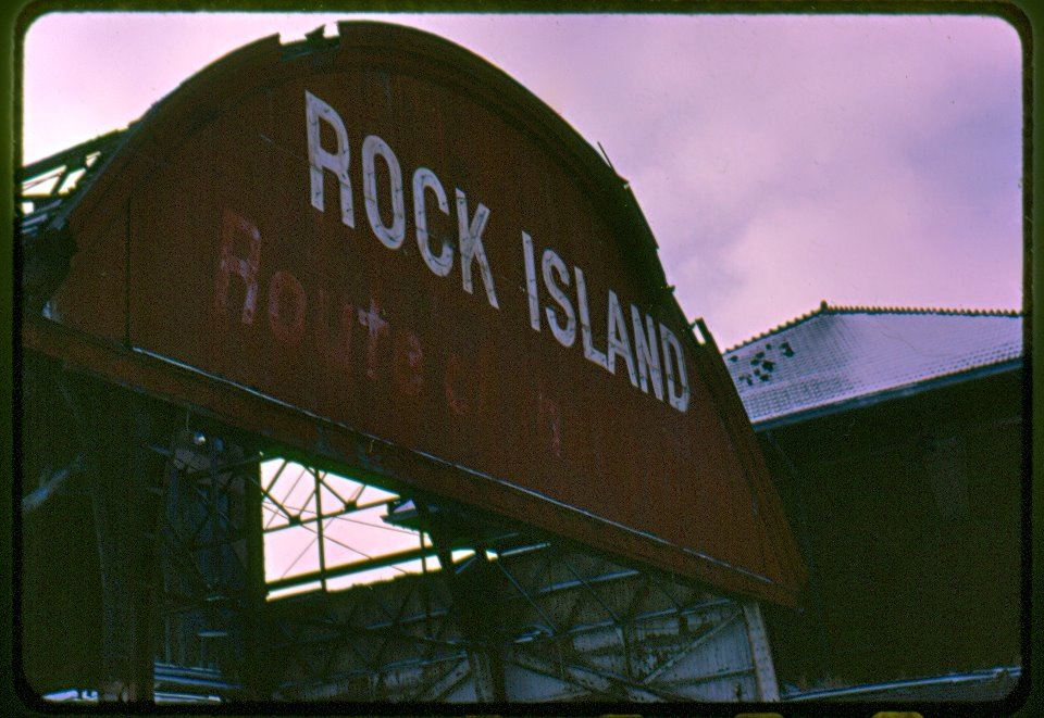A darkening sky hangs over the defunct railroad passenger depot. Although this sign was removed in 1986, the picture was taken in 1980 and bears witness to the rise and sudden, painful fall of the Chicago, Rock Island and Pacific Railroad.