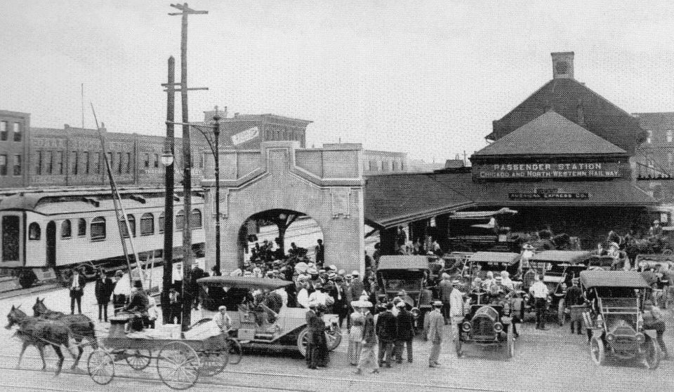 C&NW passenger depot located at E 4th St between Locust St and Grand Ave. The building was demolished in the 1950's. Photo circa 1920's.
