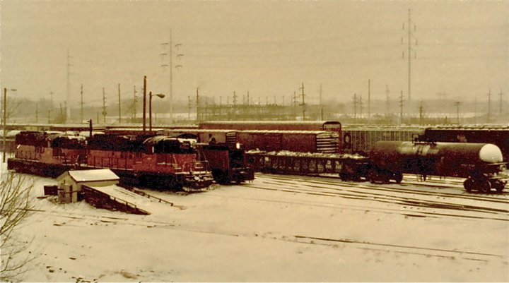 Road engines, switch engines and rolling stock sit parked in the DMUR Yard near SW 16th St in the snow. Photo circa 1979.