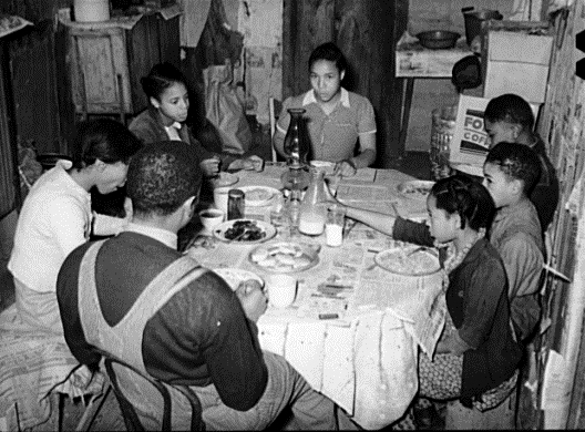 Family gathered around the dinner table during the Great Depression, courtesy of the Library of Congress