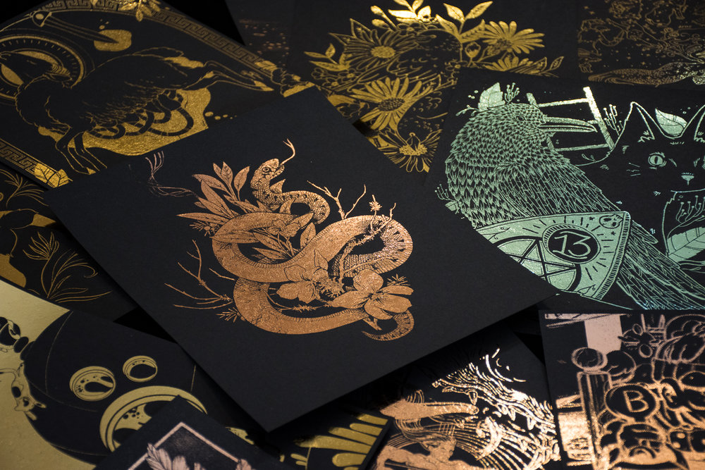 fig. 4. The rose gold foiled snake & sage print between artworks from participating artists (photo by Light Grey Art Lab)